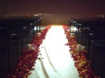 Flower strewn aisle with candles.