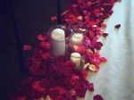 Closeup of pillar candles and rose petals.