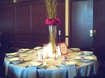 Tall arangement of manzanita branches and carnations on guest table.